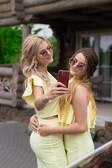 Portret van twee mooie jonge bruidsmeisjes in gele jurken in de buurt van een modieus houten huis. mensen levensstijl concept. selfie maken geschoten op mobiele telefoon glimlachen en luchtkus verzenden