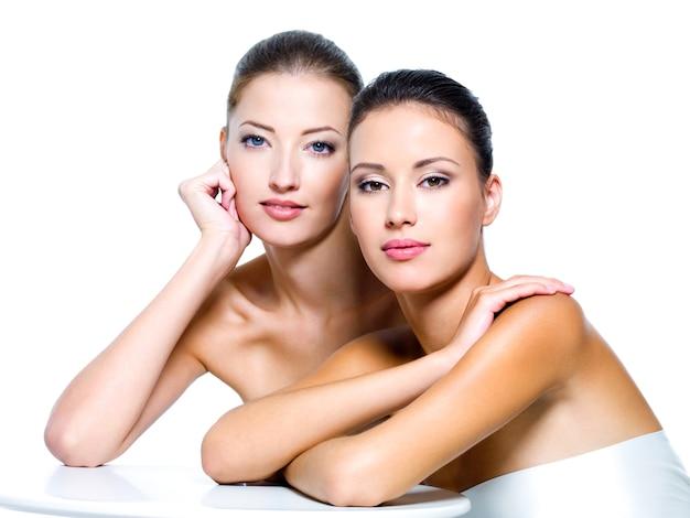 Portret van twee mooie jonge vrouwen die op wit worden geïsoleerd