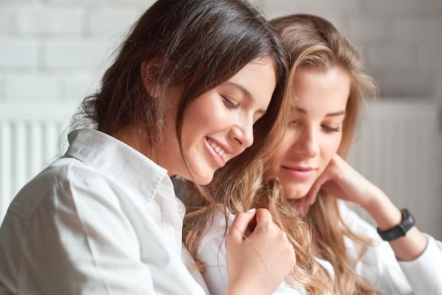 Portret van twee mooie jonge vrouwen knuffelen glimlachend vreugdevol ontspannen samen vriendschap hechting vrouwelijkheid zusters zusterschap emoties positiviteit levensstijl recreatie concept close-up.