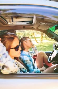 Portret van twee mooie jonge vrouwen met zonnebril die in de auto zitten tijdens een roadtrip-avontuur