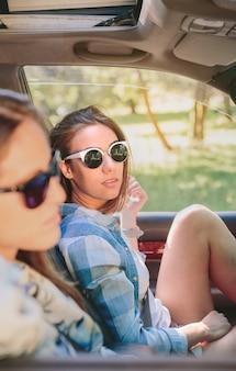 Portret van twee mooie jonge vrouwen met zonnebril die in de auto zitten