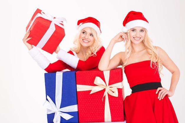 Portret van twee mooie jonge zussen tweeling in kostuums en hoeden van de kerstman met kleurrijke geschenken op witte achtergrond