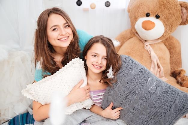 Portret van twee mooie lachende zussen met kussens die in de kinderkamer spelen
