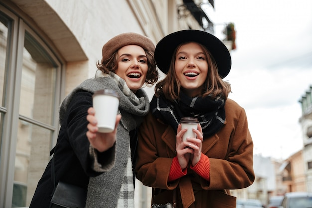 Portret van twee mooie meisjes gekleed in herfst kleding lopen
