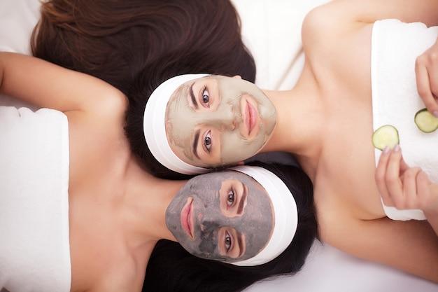 Portret van twee mooie meisjes met gezichtscrème op hun gezichten en van aangezicht tot aangezicht liggend op de vloer en het glimlachen