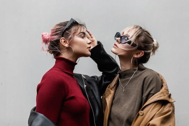 Portret van twee mooie modieuze vriendinnen meisjes in jeugdstijl met zonnebril in coole vintage leren jas met gebreide trui poseren op grijze achtergrond op straat