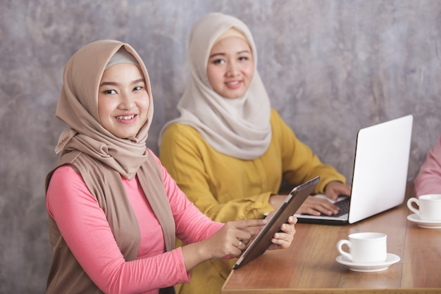 Portret van twee mooie moslimvrouwen die lacht tijdens het werken aan hun gadget