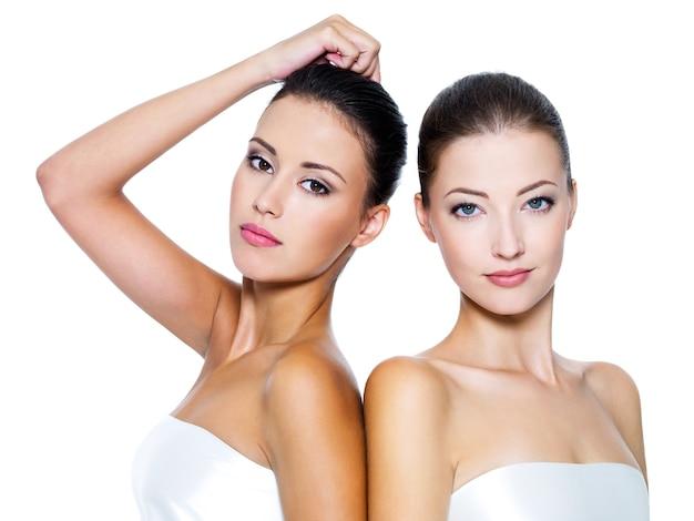 Portret van twee mooie sexy jonge vrouwen - die op wit worden geïsoleerd