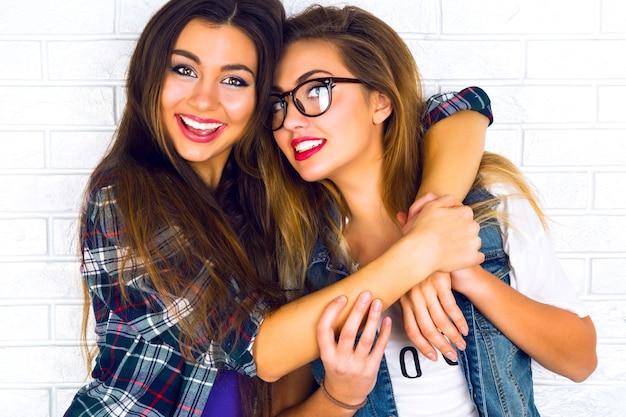 Portret van twee mooie tienermeisjes die en elkaar glimlachen koesteren