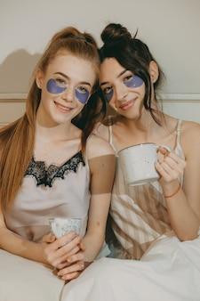 Portret van twee mooie vriendinnen terwijl het drinken van koffie ontspannen op het bed met patches op de ogen.