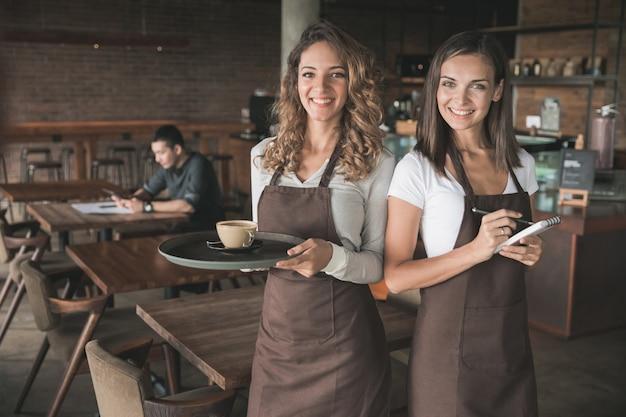 Portret van twee mooie vrouwelijke serveerster die naar camera glimlacht