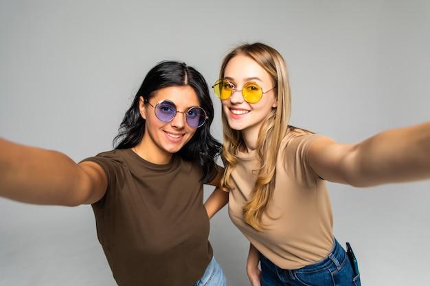 Portret van twee mooie vrouwen in zonnebrillen die staan en een selfie nemen die over een witte muur wordt geïsoleerd