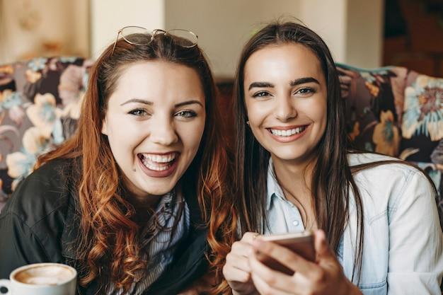 Portret van twee mooie vrouwen kijken camera lachen terwijl men een smartphone in haar hand houdt tijdens het zitten in een coffeeshop in hun vakantietijd.
