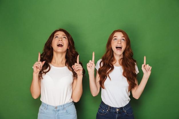Portret van twee mooie vrouwen met rood haar in witte t-shirts glimlachend en wijzende vingers omhoog van opwinding, geïsoleerd op groene achtergrond