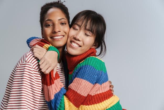 Portret van twee multinationale gelukkige vrouwen die knuffelen en lachen
