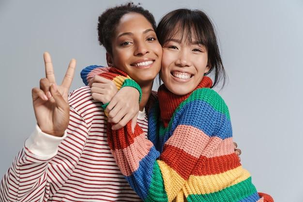 Portret van twee multinationale vrolijke vrouwen die een vredesteken knuffelen en gebaren