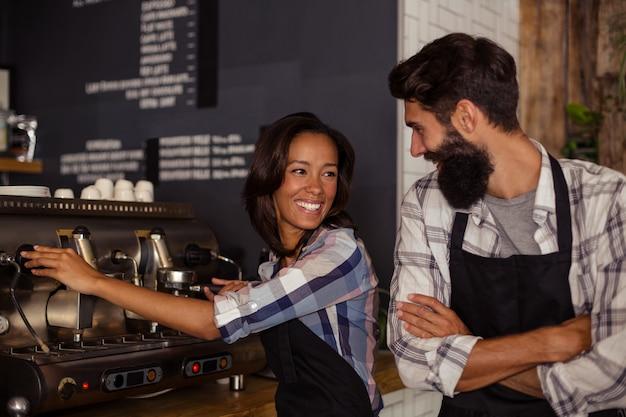 Portret van twee obers met een koffiemachine