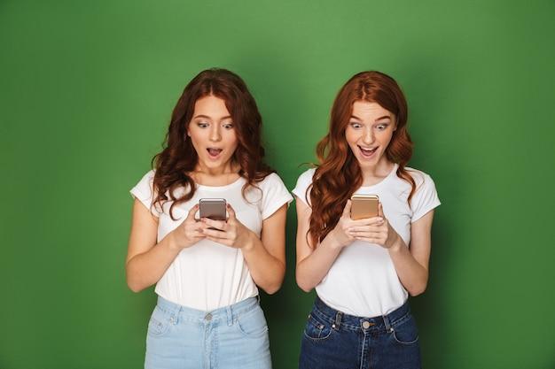 Portret van twee opgewonden roodharige vrouwen 20s poseren voor de camera en met behulp van smartphones, geïsoleerd op groene achtergrond