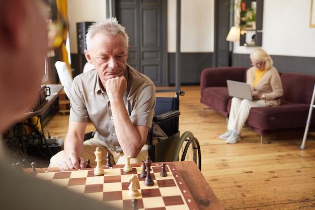 Portret van twee oudere mannen die schaken en genieten van activiteiten in een gezellige kopieerruimte in een verpleeghuis