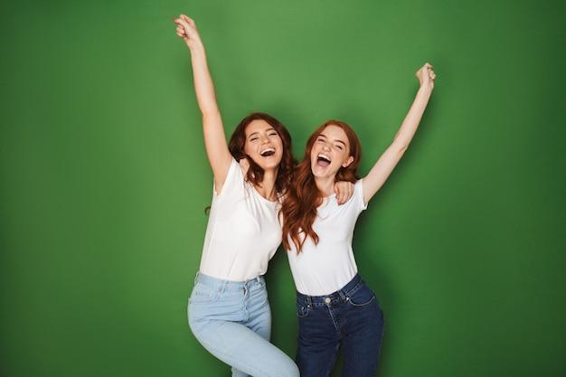 Portret van twee positieve roodharige vrouwen 20s glimlachend in de camera met handen in de lucht, geïsoleerd op groene achtergrond