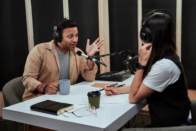 Portret van twee radiopresentatoren, man en vrouw die met elkaar praten terwijl ze een liveshow modereren in
