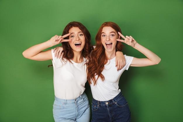 Portret van twee roodharige tienervrouwen 20s die en overwinningstekens glimlachen tonen op gezicht, geïsoleerd over groene achtergrond