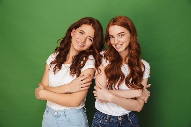 Portret van twee schattige meisjes 20s met gember haar in vrijetijdskleding glimlachend en kijken naar camera met armen gevouwen, geïsoleerd op groene achtergrond