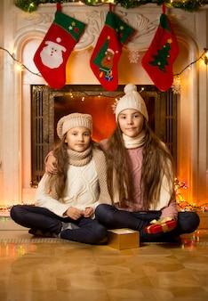 Portret van twee schattige meisjes die voor kerstmis naast een versierde open haard zitten