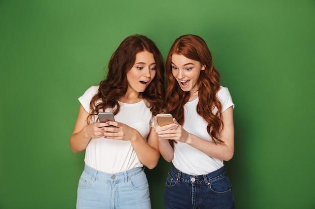Portret van twee schattige vrouwen met rood haar met behulp van mobiele telefoons met verbazing, geïsoleerd op groene achtergrond