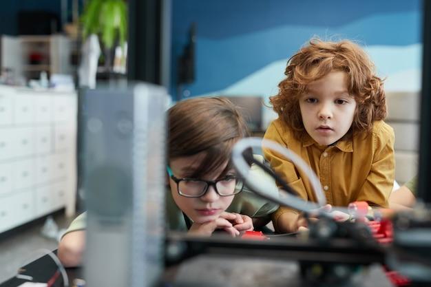 Portret van twee schooljongens die naar de 3d-printer kijken tijdens de techniekles op de moderne school, kopieer ruimte