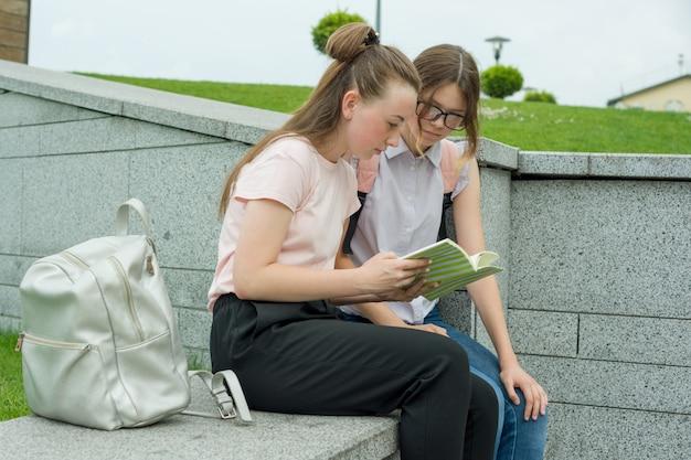 Portret van twee schoolmeisjes van tieners met schoolrugzakken en boeken.