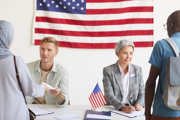 Portret van twee stembureaumedewerkers die kiezers registreren op de dag van de verkiezingen, kopie ruimte