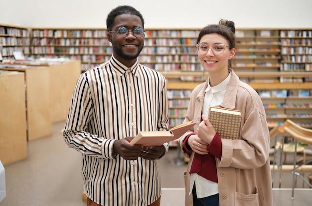 Portret van twee studenten die boeken vasthouden en naar de camera glimlachen terwijl ze in de bibliotheek staan