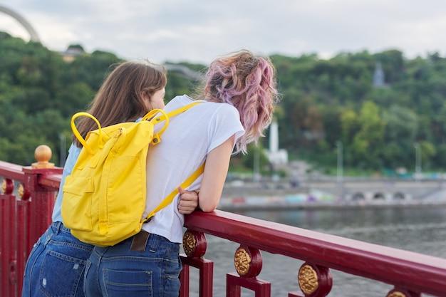 Portret van twee tienermeisjes die met hun rug op de brug over de rivier staan, vriendinnen die genieten van de zonsondergang op het wateroppervlak, praten, ontspannen. vriendschap, levensstijl, jeugd, tieners