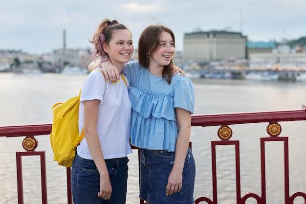 Portret van twee tienermeisjes die op de brug over de rivier staan, vrienden lopen op een zonnige zomerdag. vriendschap, levensstijl, jeugd, tieners