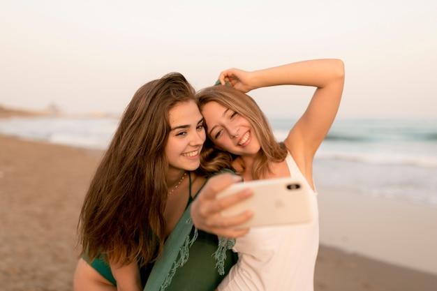 Portret van twee tienermeisjes die zelfportret op mobiele telefoon op het strand