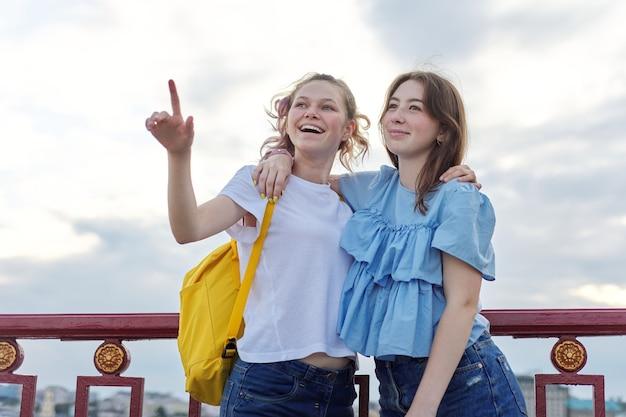 Portret van twee tienermeisjes vrienden lopend en pratend op voetgangersbrug op zonnige zomerdag. vriendschap, levensstijl, jeugd, tieners