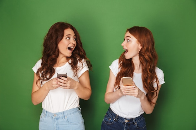Portret van twee tienervrouwen met gemberhaar die elkaar bekijken en celtelefoons gebruiken, die over groene achtergrond worden geïsoleerd