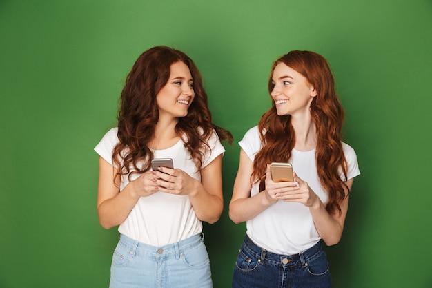 Portret van twee tienervrouwen met gemberhaar die elkaar bekijken en mobiele telefoons houden, die over groene achtergrond worden geïsoleerd