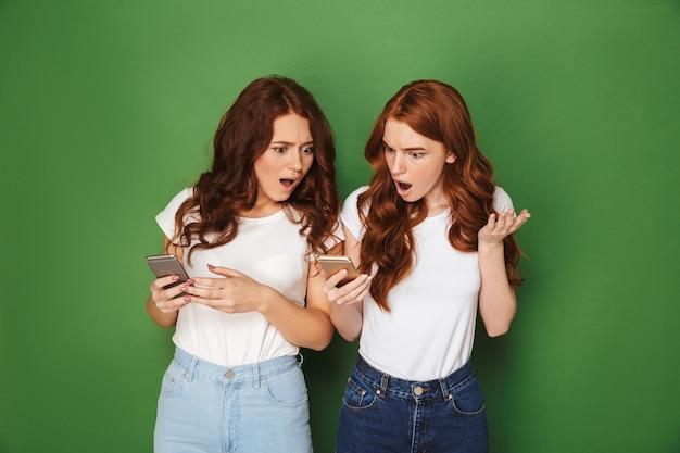 Portret van twee verontwaardigde vrouwen met rood haar die mobiele telefoons gebruiken en verontwaardiging uiten, geïsoleerd op groene achtergrond
