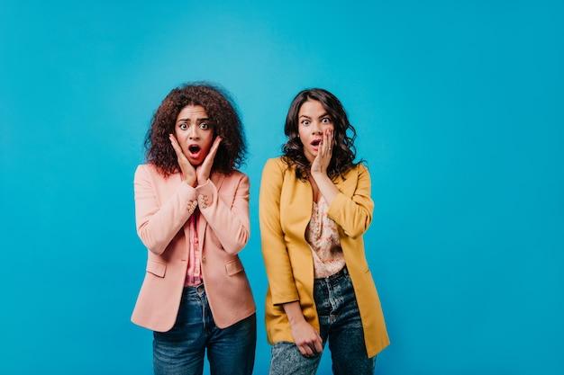 Portret van twee verraste vrouwen in kleurrijke jasjes