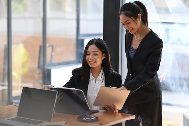 Portret van twee vriendelijke ondernemers met behulp van laptopcomputer