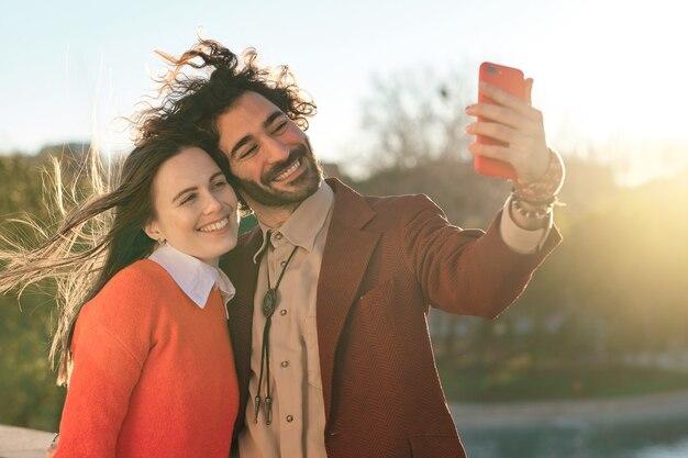 Portret van twee vrienden die goede tijd samen doorbrengen en buiten een selfie met hun mobiele telefoon nemen.