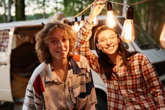 Portret van twee vrienden die naar de camera glimlachen terwijl ze plezier hebben op een picknick buitenshuis