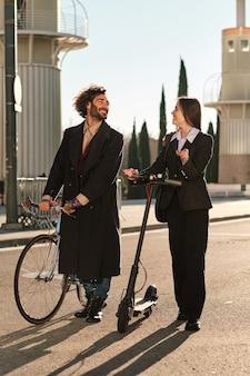 Portret van twee vrienden samen tijd doorbrengen tijdens het buiten wandelen op straat met een elektrische scooter en een fiets. stedelijk concept.