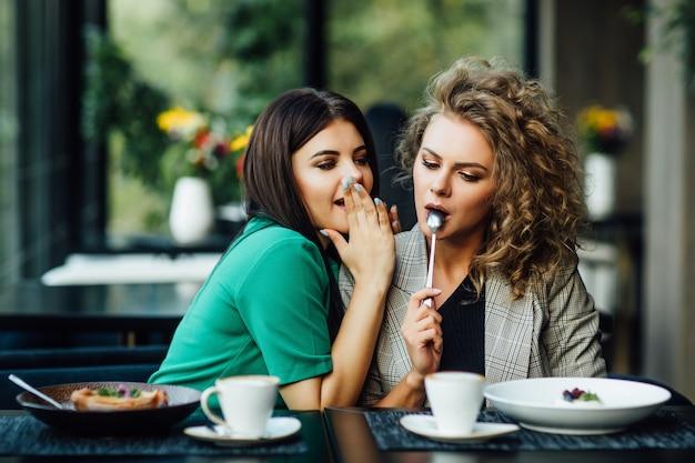 Portret van twee vriendinnen brengen samen tijd door met het drinken van koffie in het café, plezier maken door het eten van dessert, gebak. zei geheim voor andere.