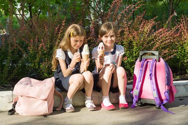 Portret van twee vriendinnenschoolmeisjes die roomijs eten