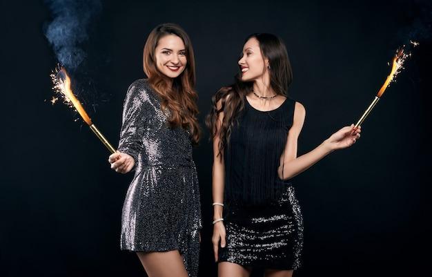 Portret van twee vrij gekke beste vrienden in modejurken poseren met vuurwerk