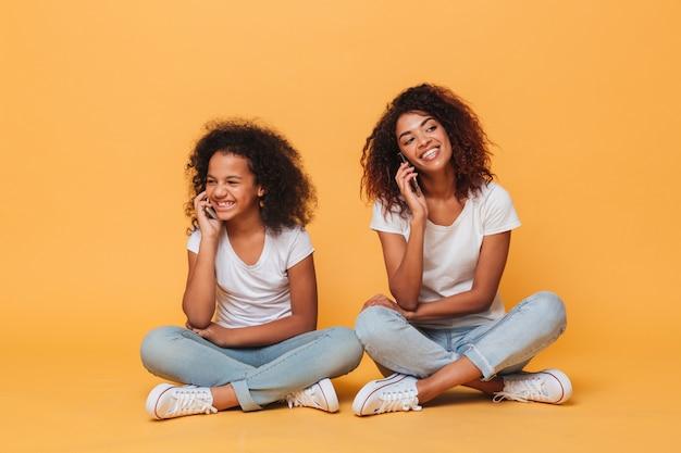 Portret van twee vrolijke afro-amerikaanse zusters die door pohone spreken