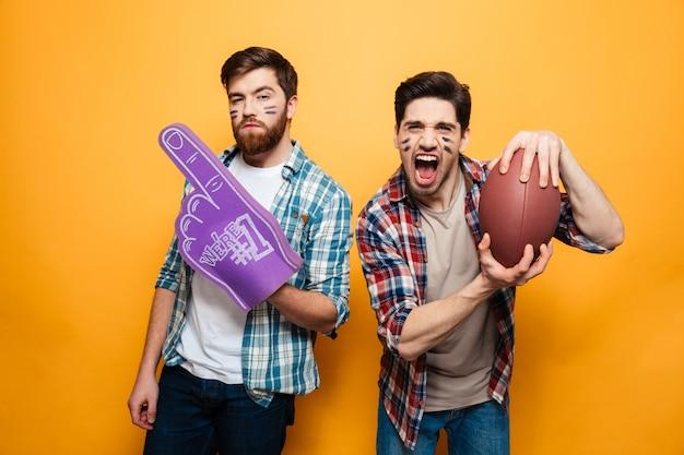Portret van twee vrolijke jonge mannen die rugbybal houden